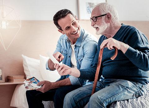 Young man shows senior man a photograph